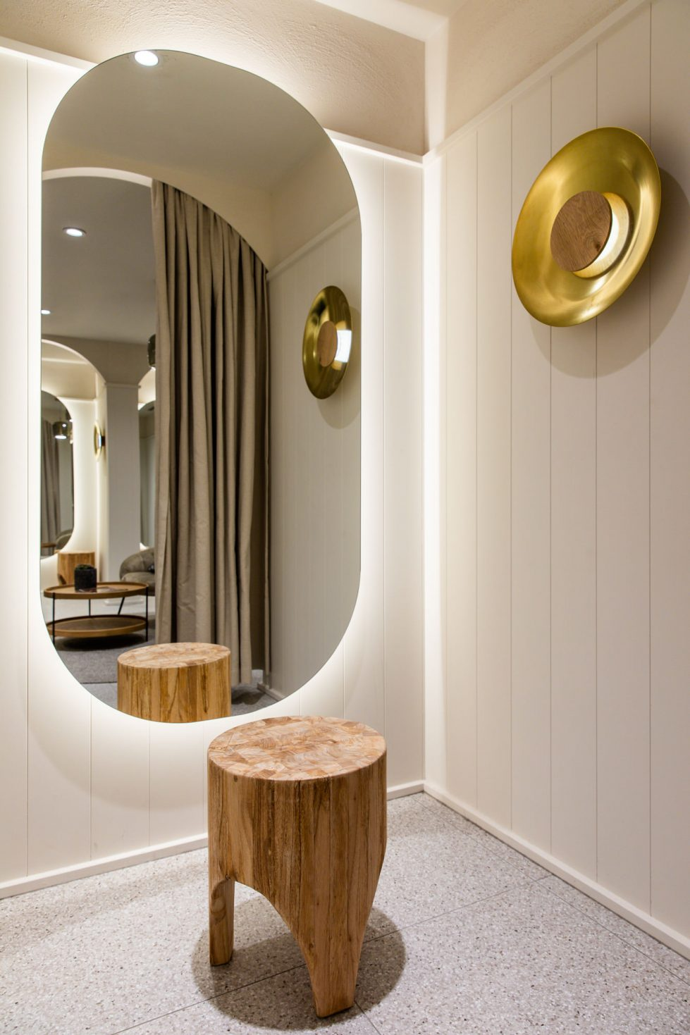 amazing backlighted mirror in a cosy and welcoming fitting room with terrazzo flooring, brass lighting and timber panelling on the walls. Interior design by design clarity